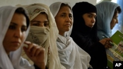 A group of Afghan women listen attentively how to count votes and seal them away to keep the country's first ever presidential election as fair as possible.