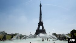 FILE - People cool themselves at the Trocadero Fountain in front of The Eiffel Tower in Paris on July 27, 2018, as a heatwave continues across northern Europe.