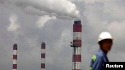 浙江寧波港的一名工人站在火力發電廠的煙囪前。
