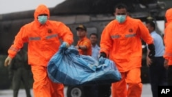 National Search and Rescue Agency personnel carry a bag containing parts of AirAsia Flight 8501 after being airlifted by a Singapore Navy Super Puma helicopter at the airport in Pangkalan Bun, Indonesia, Jan. 4, 2015.