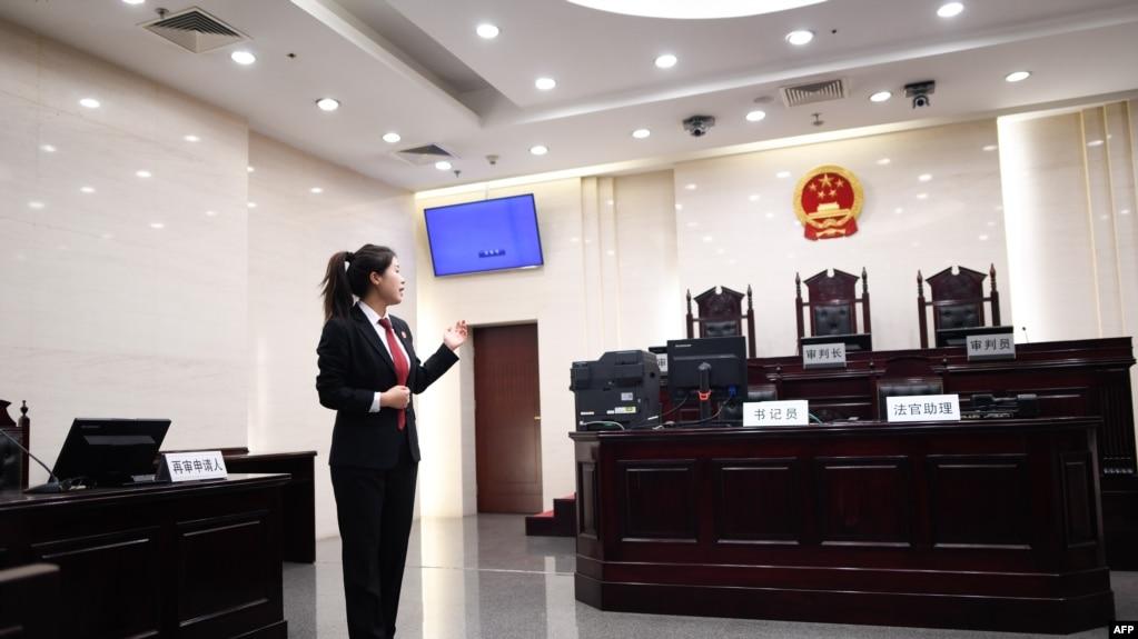 一名中国人民最高法院的工作人员站在法庭内向参观者做介绍。(2018年12月20日)