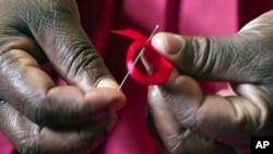 图为一名肯尼亚女子为世界艾滋病日准备红色缎带资料照