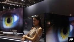 Seorang model berdiri di samping layar lebar Samsung di sebuah pameran internasional di Shanghai, 6 November 2018.
