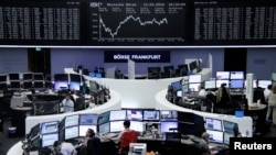 Traders work at their desks in front of the German share price index, DAX board, at the stock exchange in Frankfurt, Germany, April 12, 2016.