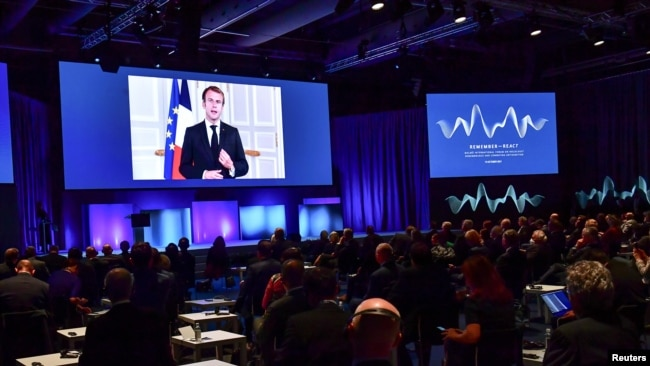 France's President Emmanuel Macron appears on a screen at the Malmo International Forum on Holocaust Remembrance and Combating Antisemitism, in Malmo, Sweden, October 13, 2021.