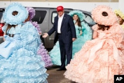 President-elect Donald Trump is greeted by the Azalea Trail Maids — 50 high school seniors chosen yearly to serve as ambassadors for the city of Mobile, Ala. — after arriving at the airport for a rally at Ladd-Peebles Stadium, Dec. 17, 2016.