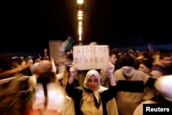 """A woman takes part in a protest demanding immediate political change, in Algiers, Algeria March 12, 2019. Her sign reads: """"System, go away."""""""