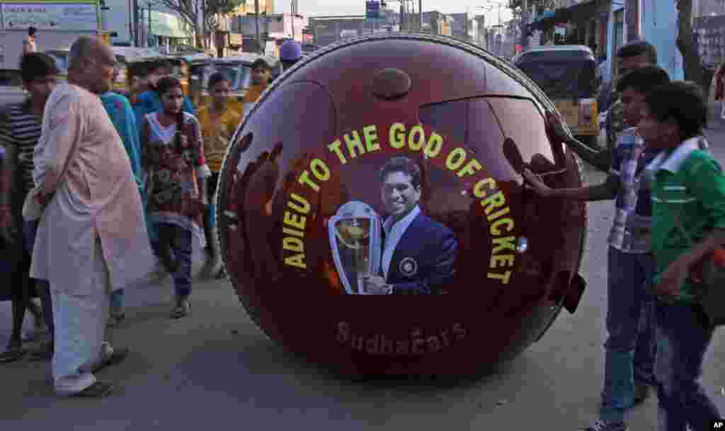 Indians look at a car shaped like a cricket ball with a portrait of Indian cricket player Sachin Tendulkar, Hyderabad, India, Nov. 14, 2013.