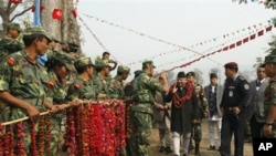 Maoist combatants greet Nepal's former Prime Minister Madhav Kumar Nepal at the Shaktikhor Maoist cantonment in Chitwan, about 80 kilometers (50 miles) southwest of Katmandu, 22 January 2011.