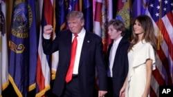 President AS terpilih Donald Trump mengacungkan tinju setelah memberikan pidato kemenangannya, didampingi istrinya Melania Trump dan putra mereka Barron, di New York (9/11). (AP/John Locher)