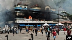 Pasar lokal dibakar oleh para demonstran selama aksi protes di kota Fakfak, provinsi Papua Barat, hari Rabu, 21 Agustus 2019. (Foto: AP/Beawiharta)