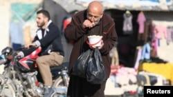 Homme ayant reçu une ration de nourriture distribuée dans une zone assiégée par les rebelles à Alep, en Syrie, le 6 novembre 2016.