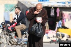 FILE - A man eats food that was distributed as aid in a rebel-held besieged area in Aleppo, Syria, Nov. 6, 2016.