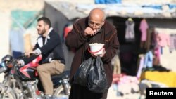 "A man eats food that was distributed as aid in a rebel-held besieged area in Aleppo, Syria, Nov. 6, 2016. ""The last food rations are being distributed as we speak,"" a U.N. official says."