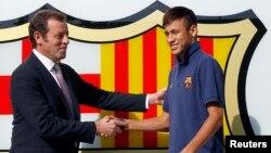 Presiden klub Barcelona Sandro Rosell (kiri) bersalaman dengan pemain asal Brazil Neymar, setelah penandatanganan kontrak Neymar dengan FC Barcelona (3 Juni 2013).