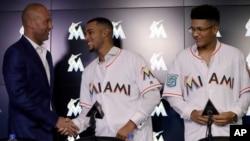 CEO Miami Marlins, Derek Jeter, kiri, berjabat tangan, berjabat tangan dengan Victor Victor Mesa, tengah, sementara saudara lelakinya Victor Mesa, Jr. mengamati dalam sebuah konferensi pers, Senin, 22 Oktober 2018 di Miami, Florida, AS (foto: AP Photo/Lynne Sladky)