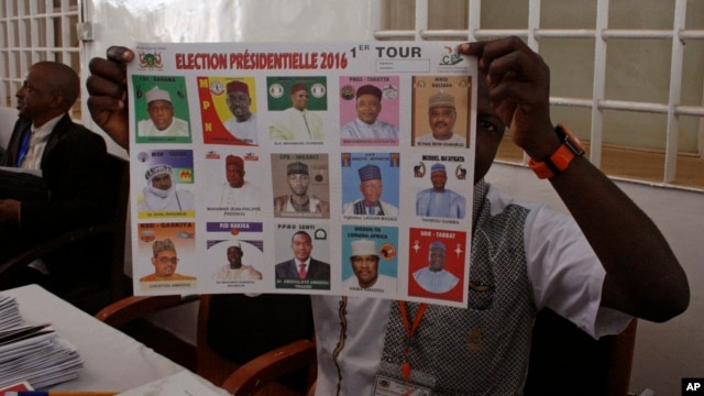 FILE - An election official shows a placard with different candidates during elections in Niamey, Niger, Feb 21, 2016.