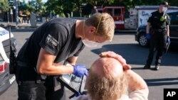Ekipe hitne pomoći pomažu čovjeku u Oregonu. (Foto: AP/Nathan Howard)