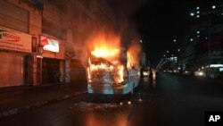 FILE - A bus stands in flames after it was set afire by opposition supporters trying to defy a ban on protests, in Dhaka, Bangladesh, Oct. 25, 2013.