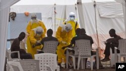 Health workers care for people with the Ebola virus, at a clinic in Monrovia, Liberia, Monday, Sept. 8, 2014.