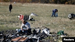 FILE - Members of a recovery team work at the site where downed Malaysia Airlines flight MH17 crashed, near the village of Hrabove, Donetsk region, eastern Ukraine, Oct. 13, 2014.