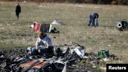 Para petugas mencari beberapa barang bukti di lokasi jatuhnya MH17 di dekat desa Hrabove, wilayah Donetsk, Ukraina Timur (13/10).