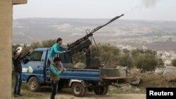 Pejuang pemberontak dari Gerakan Islamis Ahrar al-Sham menembakkan senjata anti-pesawat ke arah pasukan yang loyal terhadap Presiden Suriah Bashar al-Assad di Jabal al-Zawiya di Idlib. (Foto: Dok)
