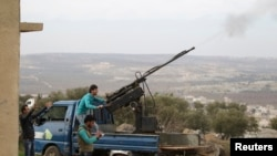 FILE - A rebel fighter from the Ahrar al-Sham Islamic Movement fires an anti-aircraft weapon towards what they said was a helicopter belonging to forces loyal to Syria's President Bashar al-Assad in Jabal al-Zawiya in the southern countryside of Idlib.