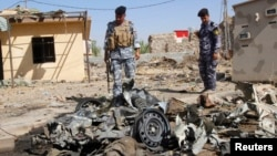 Policemen inspect the wreckage of a vehicle after a car bomb attack in Kirkuk, 250 kilometers north of Baghdad, Iraq, July 25, 2013.