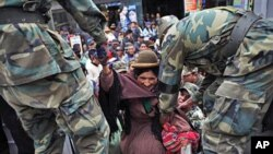 Soldiers help a woman get into a military truck during a public transportation strike in El Alto, 27 Dec 2010