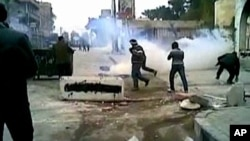 This still image taken from video off a social media website shows protesters covering their faces from tear gas being fired in a Damascus suburb by Syrian security forces, December 30, 2011.