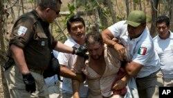 Un migrante centroamericano es detenido por agentes de inmigración mexicanos en la carretera hacia Pijijiapán, México, el lunes 22 de abril de 2019.