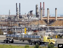 FILE - A tanker truck passes the Chevron oil refinery in Richmond, Calif.