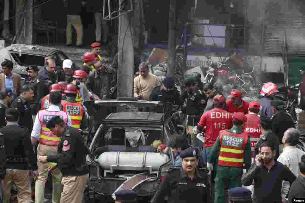 Policemen and residents gather at the site of an explosion outside the police headquarters, in Lahore, Pakistan, Feb. 17, 2015.