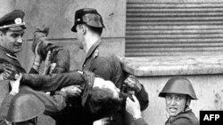 Şərqi Almanya əsgərləri, 17 avqust 1962'də, Qərbə qaçmağa çalışanda öldürdükləri Peter Fechter'in cəsədi ilə