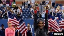 Serena Williams mengangkat piala kemenangannya setelah mengalahkan Victoria Azarenka dari Belarus (kiri) dalam final pertandingan tenis tunggal putri memperebutkan piala Amerika Terbuka di New York (8/9).