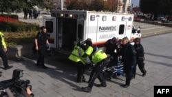 Polisi dan petugas medis membawa seorang tentara Kanada yang terluka di Ottawa, Kanada, 22 Oktober 2014.