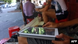 FILE - A customer uses his tablet to access the Internet at a 'wifi coffee shop' in downtown Hanoi.