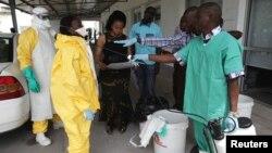 Un agent de santé pulvérise un collègue avec un désinfectant lors d'une séance de formation pour les agents de santé congolais pour lutter contre le virus Ebola à Kinshasa le 21 octobre 2014.