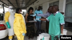 FILE - A health worker sprays a colleague with disinfectant during a training session for Congolese health workers to deal with Ebola virus in Kinshasa October 21, 2014.