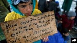 Un garçon migrant montre une bannière disant qu'il veut se rendre en Allemagne plutôt que dans des camps mis en place par la Turquie, lors d'une manifestation à Idomeni en Grèce, exigeant l'ouverture de la frontière entre la Grèce et la Macédoine, le 23 Mars 2016 (AP Photo/Darko Vojinovic)