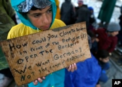 A migrant boy shows a banner saying he wants to travel to Germany rather than camps set up by Turkey, during a protest demanding the opening of the border between Greece and Macedonia in the northern Greek border station of Idomeni, Greece, March 23, 201