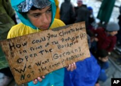 A migrant boy shows a banner saying he wants to travel to Germany rather than camps set up by Turkey, during a protest demanding the opening of the border between Greece and Macedonia in the northern Greek border station of Idomeni, Greece.