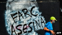 Un hombre pasa corriendo junto a un mural contra el expresidente colombiano (2002-2010) Álvaro Uribe, que fue pintado y ahora muestra un graffiti contra las FARC, una vez grupo guerrillero y ahora el partido político.
