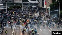 在香港湾仔地区的一次反政府示威期间,抗议者逃避警方释放的催泪弹。(2019年10月6日)