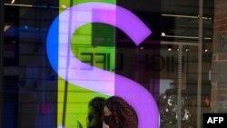 Una mujer usando máscara de protección habla por teléfono frente a una tienda en Ciudad México, México, el 1 de diciembre de 2020.