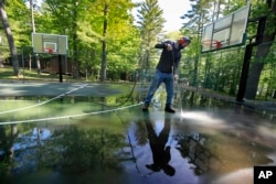 In this Thursday, June 4, 2020 photo, trip leader Gordon Anderson power washes an outdoor basketball court at the Camp Winnebago summer camp in Fayette, Maine. The boys camp is going ahead with plans to open with a reduction in the number of campers.