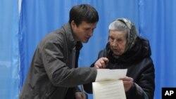 Cử tri cao tuổi được giúp đỡ tại một địa điểm bầu cử ở Kiev, Ukraina, ngày 28/10/2012