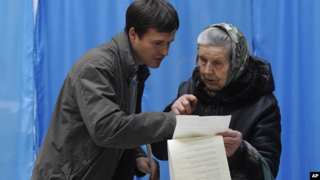 A young man helps an elderly voter read her voting ballot at a polling station  in Kiev, Ukraine, Sunday, Oct. 28, 2012.