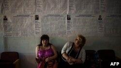 Dua orang perempuan duduk dekat poster pemilu di tempat pemungutan suara di Krasnoarmiisk, provinsi Donetsk, Ukraina timur (24/5).